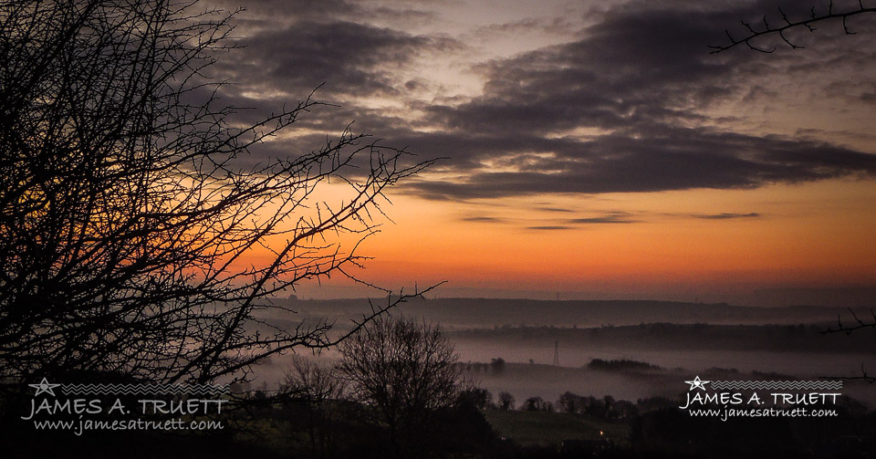 Sunrise with and Irish Mist over a valley in County Clare.